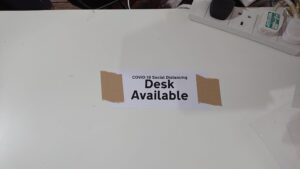 "Desk with a ""Desk Available"" sign"