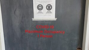 "Door with ""COVID19 maximum occupancy 1 person"" sign"